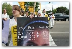 Protestors march around Chevron grounds in San Ramon with stock tickers depicting that Chevron's stock goes up as quality of life goes down  -> Click to enlarge