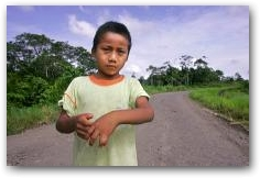 Nine-year-old, Jairo Yumbo, stands on the road in front of his home in the village