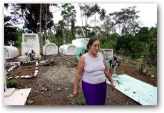 Juana Apolo walks out of a cemetary in Andina where her father, brother and sister are buried, all of whom died of cancer  -> Click to enlarge
