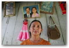 At her home in Andina, Amanda Armijos, sister-in-law of Juana Apolo, stands in front of a photo of herself and husband Saul Apolo who died of stomach cancer  -> Click to enlarge