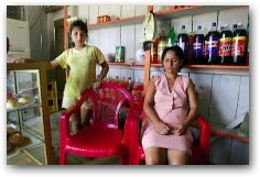 Colon cancer victim Maruja Garrido sits with her fifteen-year-old daughter Nelly at their small store in Taracoa  -> Click to enlarge