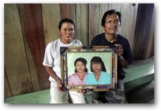 Jose Miguel Mashumar and Maria Claudia Antuash sit with a portrait of their deceased daughters Rosa and Maria Graciela at their home on the Via Auca  -> Click to enlarge