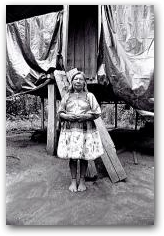 Cofan elder woman standing outside of her home in Dureno village  -> Click to enlarge