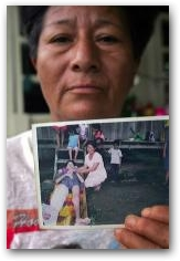 Dolores Morales holds a photo of her nineteen-year-old son Pedro who died of a cancerous tumor at her home in Sacha Central  -> Click to enlarge