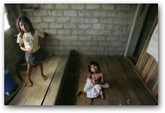 With her eight-year-old sister Alexandra Raquel at left, fifteen-year-old Myra Chicaiza sits on the floor of her home in Dureno  -> Click to enlarge