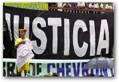 "A Secoya elder stands in front of a banner reading ""Justice"" during a demonstration at the start of the trial against ChevronTexaco in Lago Agrio  -> Click to enlarge"